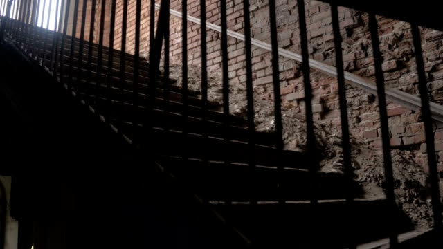 close up: detail of crumbling wooden staircase in decaying residential building - parapetto barriera video stock e b–roll