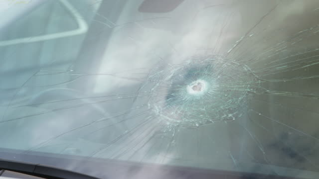 detail of damage to windscreen of car shattered by vandalism - rack focus video stock e b–roll