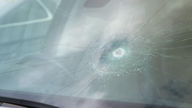 vidéos et rushes de détail des dommages au pare-brise de la voiture brisée par le vandalisme - pare brise