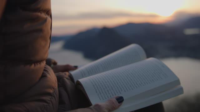 stockvideo's en b-roll-footage met detail van vrouwelijke handen houden boek bij zonsondergang in uitkijkpunt - mid volwassen vrouw