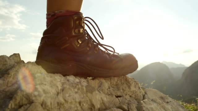 vídeos de stock e filmes b-roll de close up: detail of female hiking boots and hiking downhill on rough terrain - bota
