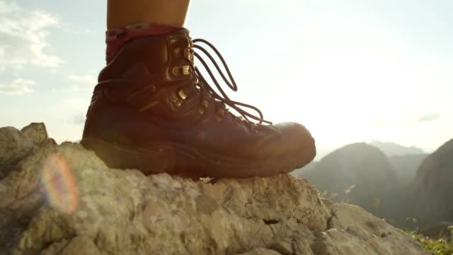 vidéos et rushes de close up: détail des femmes bottes de randonnée et de descente de randonnée sur terrain accidenté - bottes