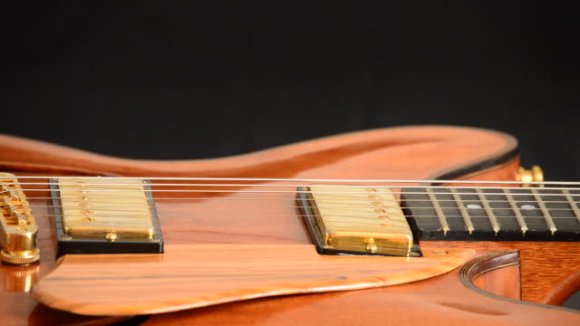 Detail of fingerboard, frets, strings, bridge and wood of electric guitar rotating at black background video