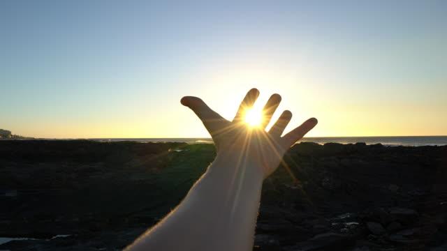 夕日の光線をカップに伸ばして手の詳細 - 指点の映像素材/bロール