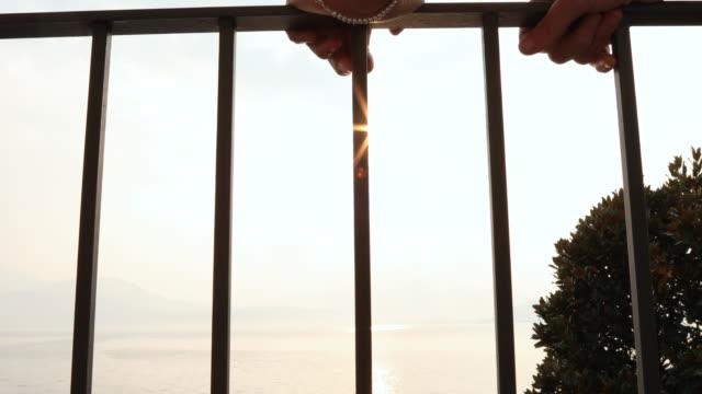 vídeos de stock e filmes b-roll de detail of hands holding railing at sunrise - lago maggiore