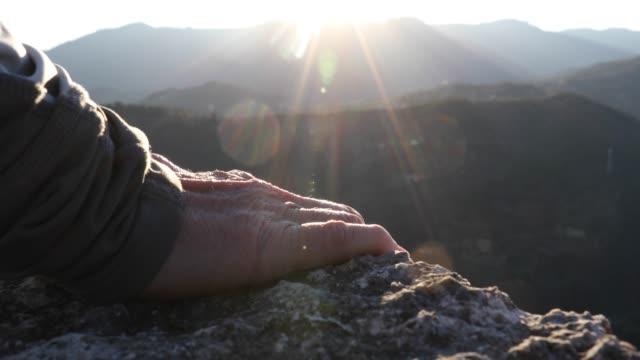vidéos et rushes de détail des mains atteignant le bord de falaise au-dessus de la vallée, au lever du soleil - un seul homme d'âge mûr