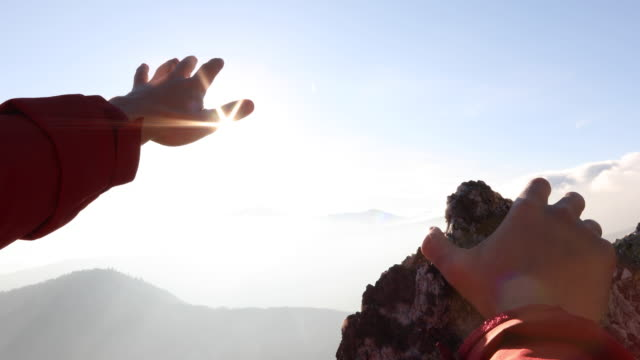 detail of hiker's hand reaching over mountains at sunrise - avvicinarsi video stock e b–roll