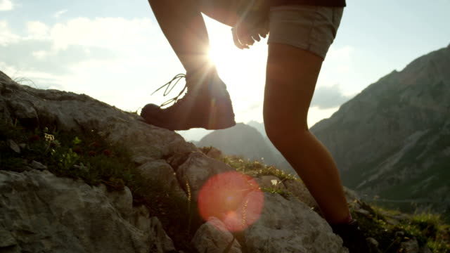 CLOSE UP: Detail of leather mountain shoes and woman climbing steep mountaintop