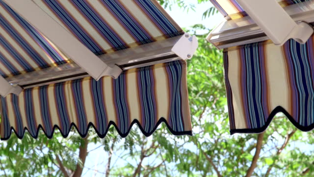 Detail of modern retractable striped awnings over sunny blue sea video