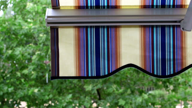 Detail of modern striped awnings in the rain video