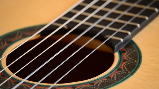 Detail of mouth, strings, frets, body of spanish classic guitar with red mouth rotating at black background video