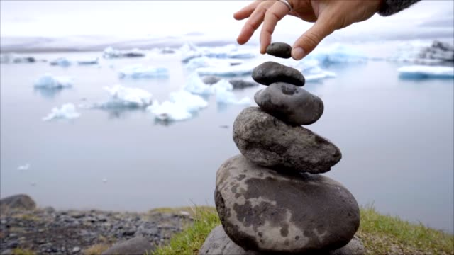 szczegóły osoby układającej skały nad laguną lodowcową na islandii - dokładność filmów i materiałów b-roll
