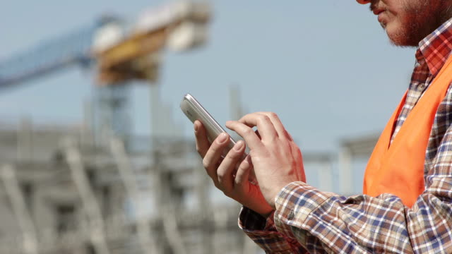 Detail of Site manager's hands using smartphone