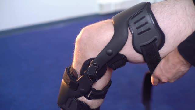 vídeos y material grabado en eventos de stock de detalle de la mitad inferior del hombre ajustando un soporte de pierna de apoyo. - columna vertebral humana