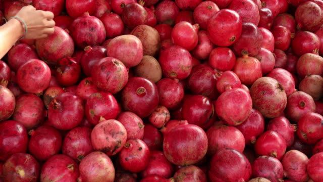 vídeos de stock e filmes b-roll de detail of woman's hand choosing ripe pomegranate from pile - romã