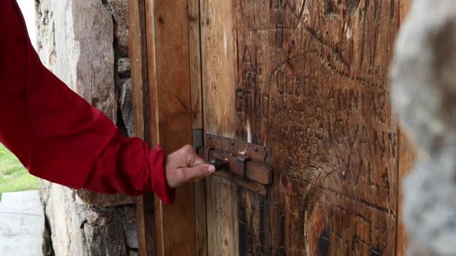 Detail of woman's hand opening hut door