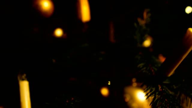 vídeos y material grabado en eventos de stock de configuración de bola de vidrio de tiro detalle en árbol de navidad y velas encendidas, noche - advent