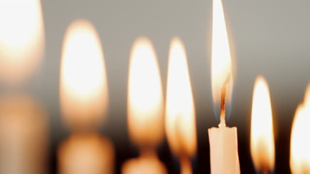 vídeos y material grabado en eventos de stock de plano de detalle de las llamas en un grupo de velas blancas, quema para la festividad judía de janucá, que son soplados hacia fuera, enfoque selectivo - hanukkah