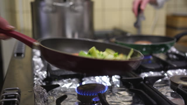 Detail shot of vegetables being sauteed in a kitchen