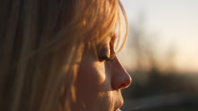 detail shot of woman's eye, her hair blowing in the wind while she meditates - spettinato video stock e b–roll