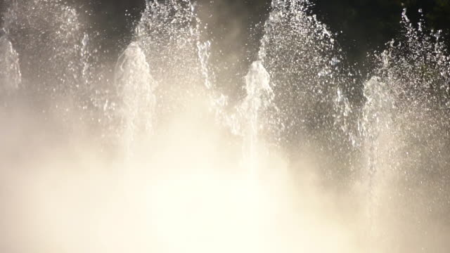Detail slow motion of artesian fountain in the park Detail slow motion of artesian fountain with misty vapors in the park cooling on a hot summer day, with several threads of water that goes high. fountains stock videos & royalty-free footage