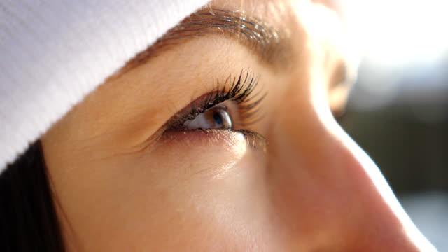 周りを見回す女性茶色の目の詳細図。魅力的な茶色の目の女の子が点滅し、美しい冬の景色を眺めることができます。美しい晴れた日を楽しんでいる女性。健康的なコンセプト。スローモー� - 人の肌点の映像素材/bロール