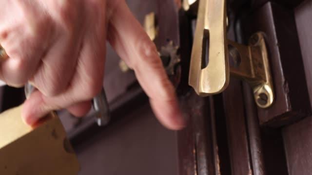 Detail view of woman closing door, applying lock