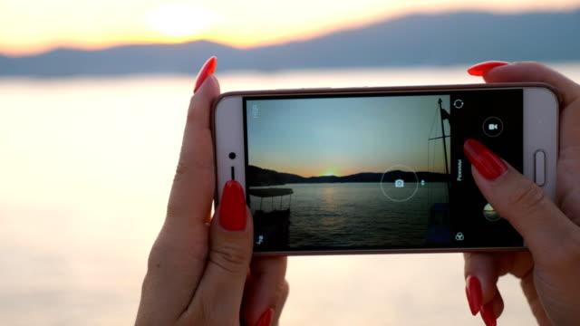 vidéos et rushes de vue détaillée sur les mains femelles retenant le smartphone et faisant la photo du paysage marin scénique au coucher du soleil. fille utilisant le téléphone pour obtenir de belles images du paysage marin. fond flou. - photophone