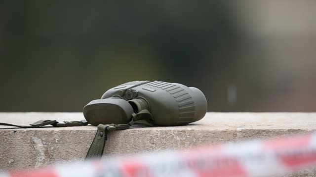 Detail with a military green binoculars behind a do not cross tape