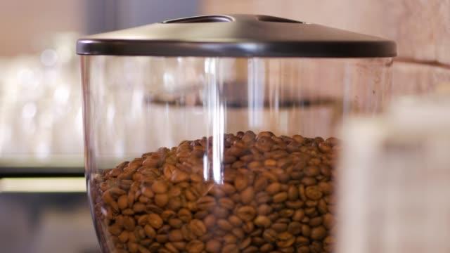 ぼやけた背景にコーヒーグラインダーマシンでのロブスタアラビカコーヒー豆の山の詳細なクローズアップビュー - バリスタ点の映像素材/bロール