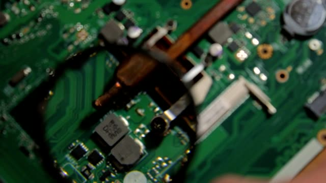 A detailed inspection of the laptop's motherboard closeup with a magnifying glass video