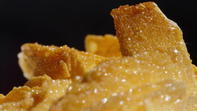 MACRO DOF: Detailed shot of a rough surfaced golden barite vanadinite gemstone. video