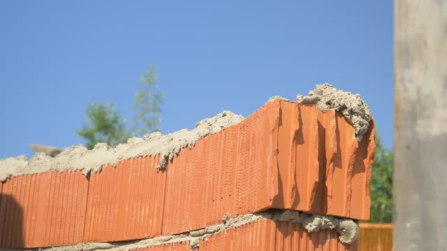 CLOSE UP: Detailed shot of builder's hands as he lays bricks on a sunny day.