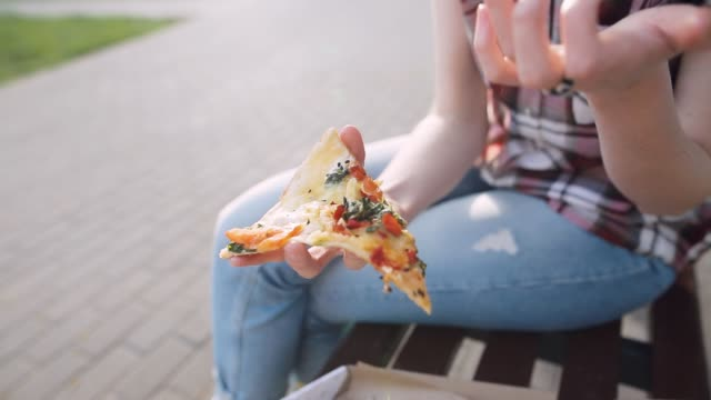 Detailed shot of girl takes a piece of fresh pizza and eats it. Closeup shot. Selective focus