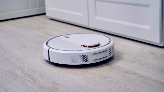 Detailed view on a self-moving robotic vacuum on the floor. A camera follows a round white robotic cleaner in a close view. appliance stock videos & royalty-free footage