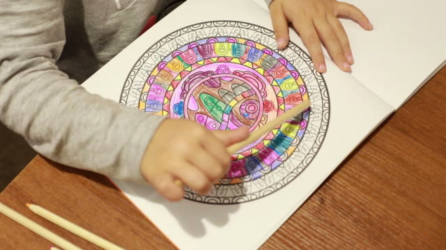 vídeos de stock e filmes b-roll de details with the hands of a 4 years old girl coloring with pencils in a children's coloring book - mandala