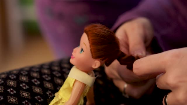 Details with the hands of a mother brushing and arranging the hair of her little daughter's doll.