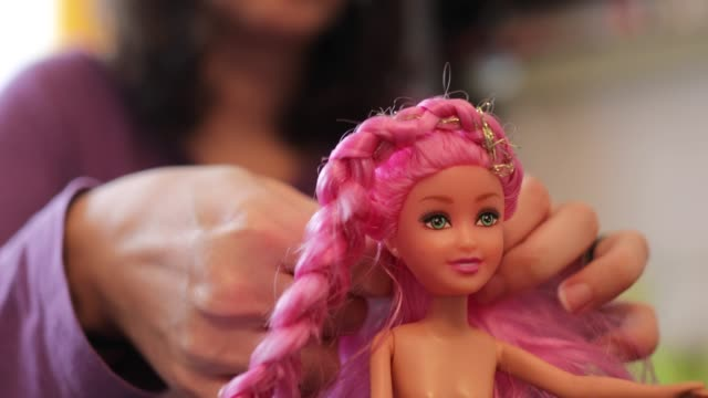 Details with the hands of a mother brushing and arranging the hair of her little daughter's doll. Details with the hands of a mother brushing and arranging the hair of her little daughter's doll. doll stock videos & royalty-free footage