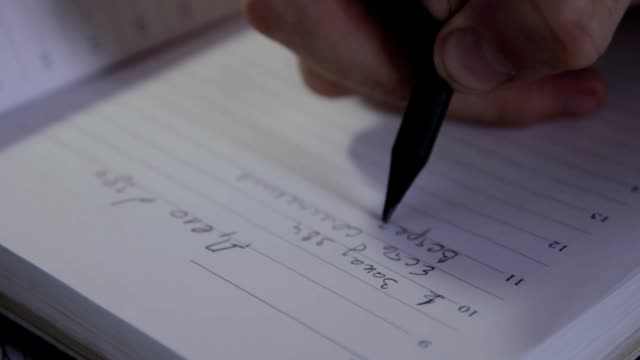 Detective is writing a checklist for work in his diary on russian language Detective makes a plan of work of the case. Closeup of man's hands is writing a checklist for work in his diary on russian language. detective stock videos & royalty-free footage