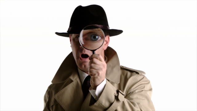 Detective looks through magnifyer Detective looks through a magnifying glass and displays different expressions. magnifying glass stock videos & royalty-free footage