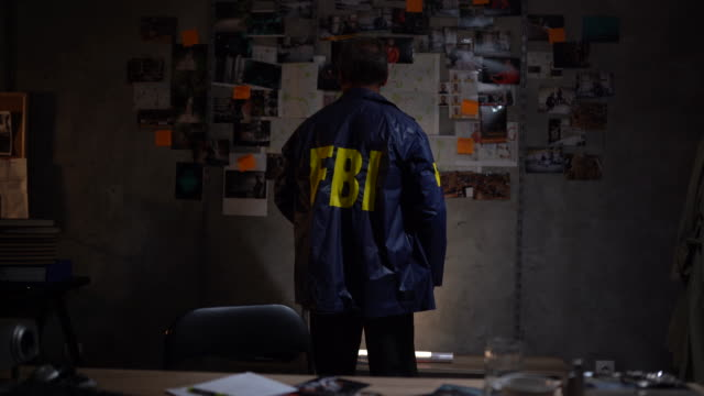 FBI detective solving a crime FBI police detective working late and trying to solve a crime by linking evidences on the wall detective stock videos & royalty-free footage