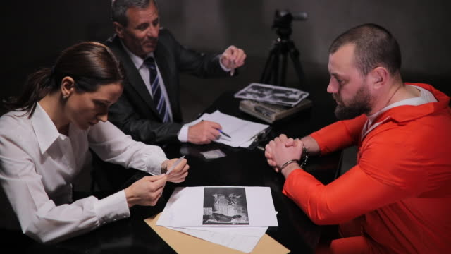 Detectives and male prisoner in interrogation room Three people, man and woman detectives investigating a man prisoner in dark investigation room. police interview stock videos & royalty-free footage