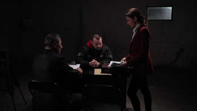 Detectives interrogating a male prisoner