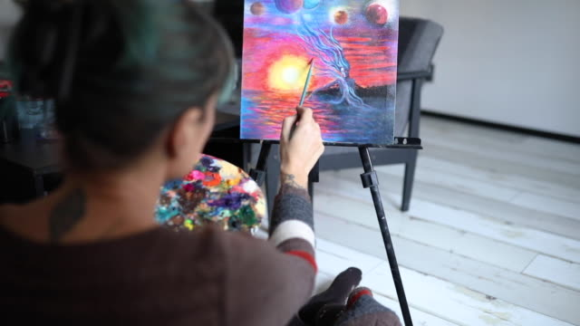 Determinated modern female artist painting in her art studio Rear close up view of female unrecognizable painter working on abstract painting blue hair stock videos & royalty-free footage