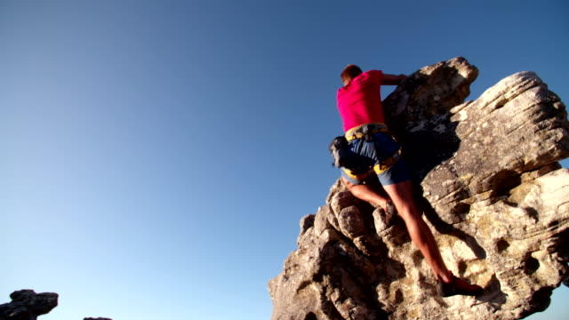 Determination in rock climbing man's face during ascent of mountain video