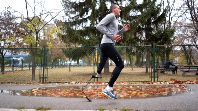 Determined amputee athlete running outdoors Young and athletic man with a artificial leg, exercising outdoors, living a healthy lifestyle recovering. artificial limb stock videos & royalty-free footage