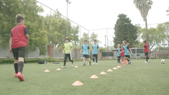 Determined boys and girls practicing soccer drills on field video