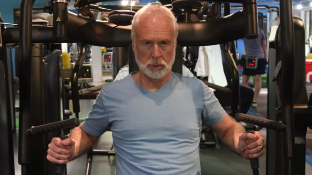 Determined caucasian male working on upper body strength at gym senior man at gym on muscle building equipment health club stock videos & royalty-free footage