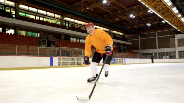 stockvideo's en b-roll-footage met vastbesloten ijshockeyspeler aan te pakken en schieten op doel tijdens sport opleiding in een ijsbaan. slow-motion. - samen sporten