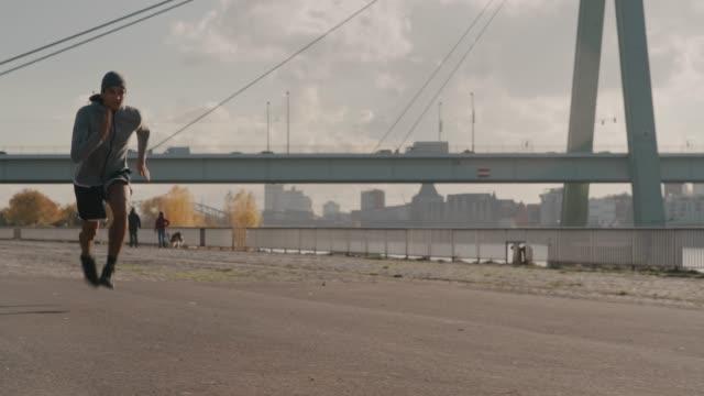 determined male athlete running on city street - rozgrzewka filmów i materiałów b-roll